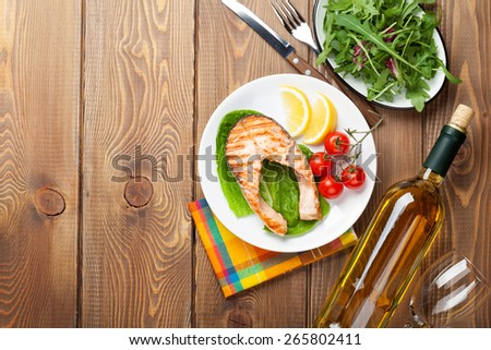 Grilled salmon and whtie wine on wooden table. Top view with copy space - stock photo