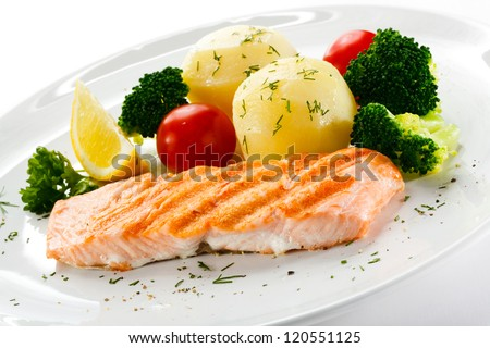 Grilled salmon, boiled potatoes and vegetables - stock photo