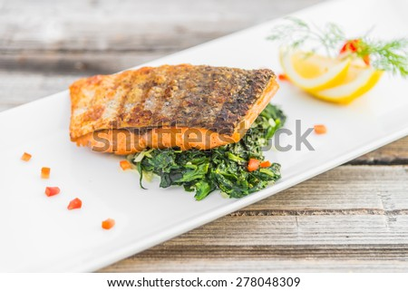 Grilled salmon fillet fish steak with lemon on white plate - stock photo
