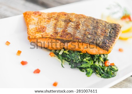 Grilled salmon fillet fish steak with lemon on white plate