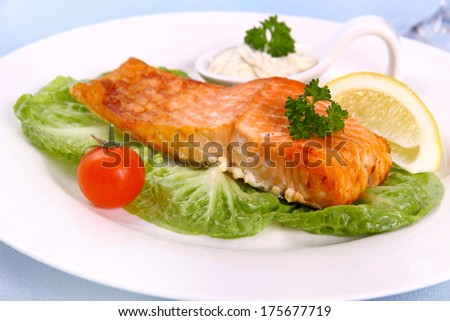 Grilled salmon fillet with salad, tomato and lemon, close up