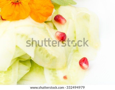Grilled salmon fillet with sliced cucumbers and roasted potatoes. With fresh flower on top as a decoration and pomegranat seeds. Macro. Photo can be used as a whole background. - stock photo