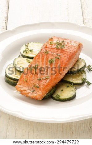 grilled salmon fillet with zucchini and thyme on a white plate - stock photo