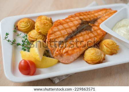 Grilled salmon fish steak with potato crockets, lemon and tomato with ...