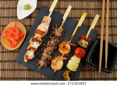 Grilled Salmon, Octopuses, Shrimps and Vegetables on Wooden Stick with Ginger, Soy Sauce and Wasabi on Straw Mat background. Top View - stock photo