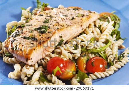 grilled salmon on blue plate with tomato and arugula pasta salad - stock photo
