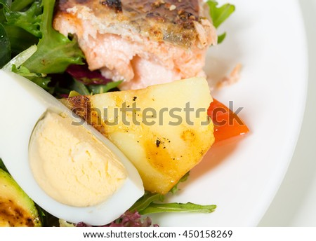 Grilled salmon salad with vegetables and eggs. Macro. Photo can be used as a whole background.