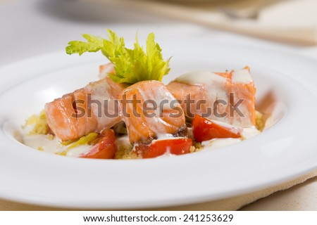 Grilled salmon seafood starter with small portions of fillet, drizzled with a creamy savory sauce and served with lettuce and tomato - stock photo