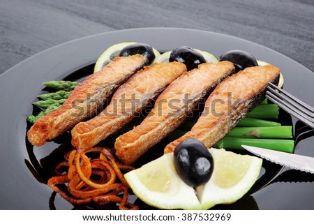 grilled salmon slices with asparagus lemon olives and cutlery on black plate over dark wooden table - stock photo