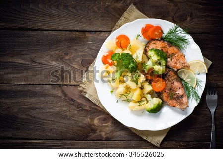 Grilled salmon steak garnished with vegetables. Top view, style rustic. - stock photo