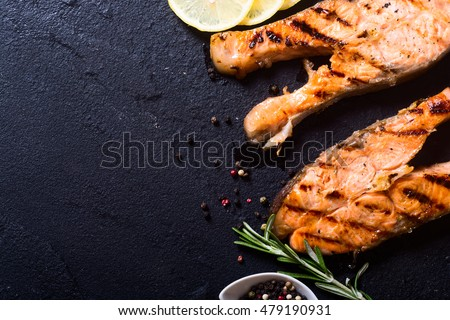 grilled salmon steak on stone with spices