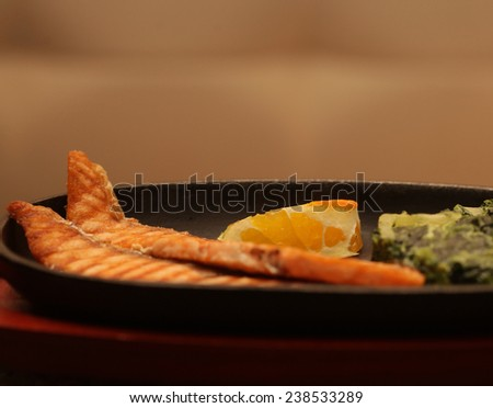Grilled salmon steak served with spinach - stock photo
