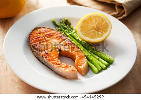 grilled salmon steak with asparagus and lemon in plate