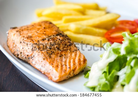 Grilled salmon steak with french fries tomatoes and vegetables - stock photo