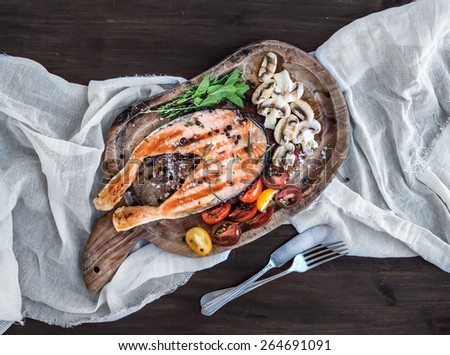 Grilled salmon steak with fresh herbs, roasted mushrooms, cherry-tomatoes and spices on a rustic wooden board over white kitchen towel and dark wood background. Top view - stock photo