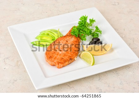 Grilled salmon steak with greens,onion, lemon, lime and olive - stock photo