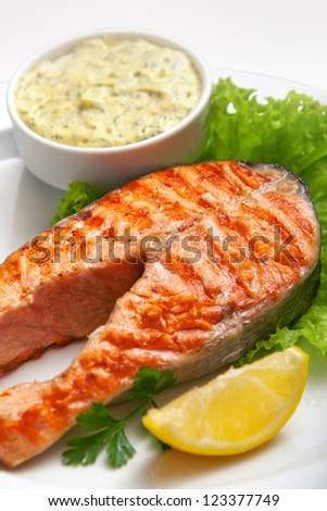 grilled salmon steak with sauce, parsley and lemon