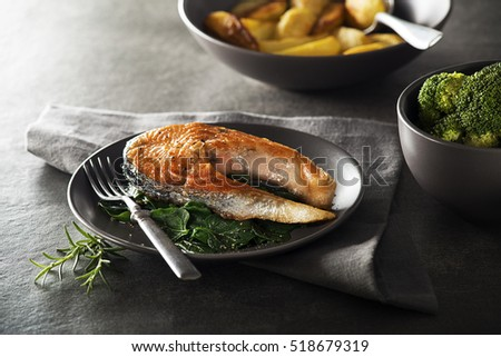 Grilled salmon steak with vegetables on dark background.