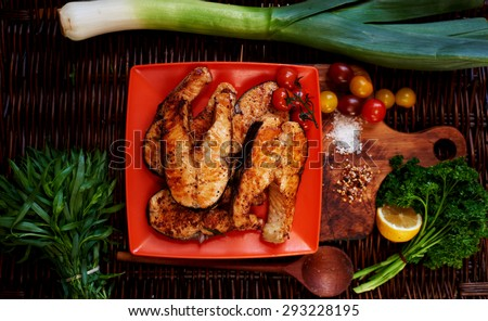 Grilled salmon steaks for lunch and salmon are in bright red square plate, lying next to vegetables salad tomatoes, onions, parsley and rosemary - stock photo