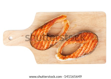 Grilled salmon steaks on cutting board. Isolated on white background - stock photo