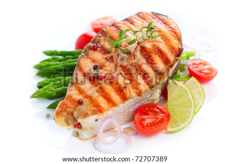 grilled salmon with asparagus and cherry tomatoes on white plate - stock photo
