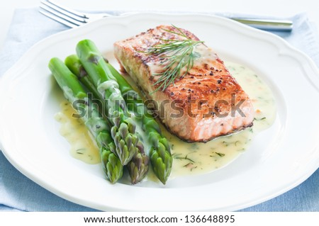 Grilled salmon with asparagus and dill sauce on white plate - stock photo