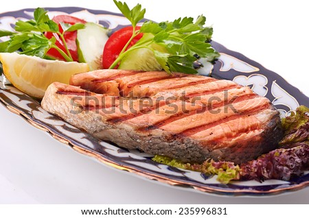 grilled salmon with asparagus, pea, yellow peppers, carrots and spring onions on white plate - stock photo