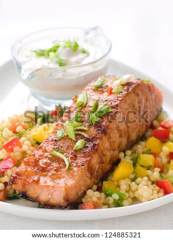 Grilled salmon with couscous  and sauce, selective focus - stock photo