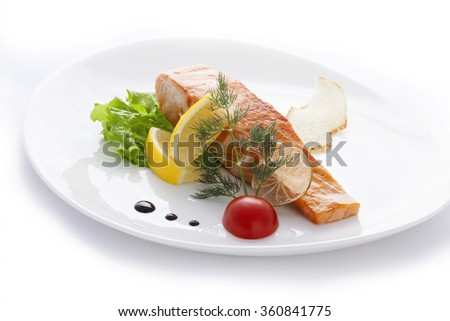 grilled salmon with lemon and cherry tomatoes on a white plate
