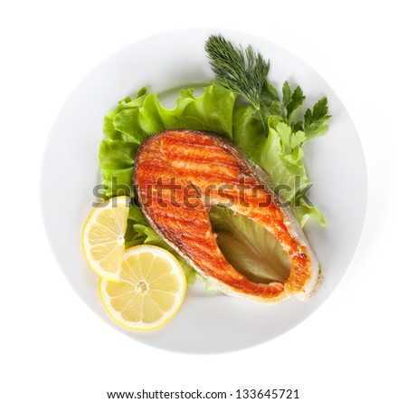 Grilled salmon with lemon slices and herbs on plate. Isolated on white background - stock photo