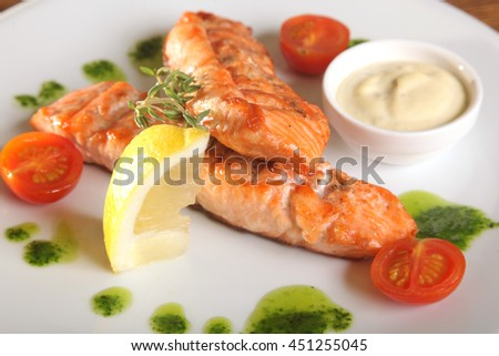 Grilled Salmon with lemon with sauce on plate