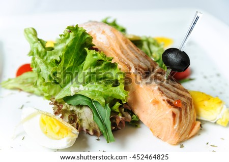 Grilled salmon with lettuce on a white plate.