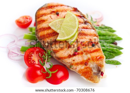 Grilled salmon with lime, asparagus and cherry tomatoes on white plate - stock photo
