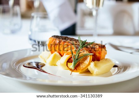 Grilled salmon with potato puree and rosemary leaves on white plate. Selective focus and shallow DOF - stock photo
