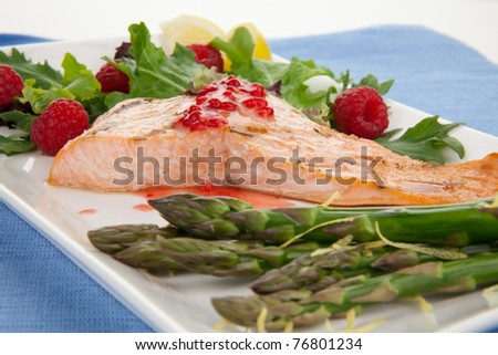 Grilled salmon with raspberry dressing served with asparagus and green salad, healthy meal. - stock photo