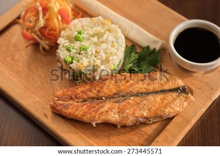 Grilled salmon with rice and vegetables at wooden table - stock photo