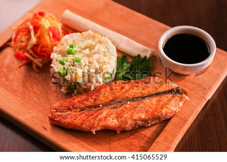 Grilled salmon with rice and vegetables at wooden table