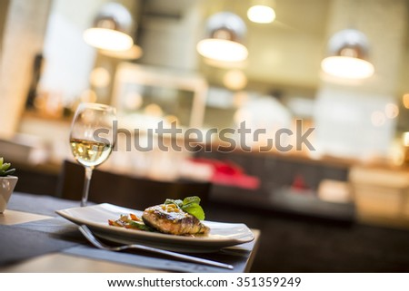 Grilled salmon with sauce and herbs served at restaurant