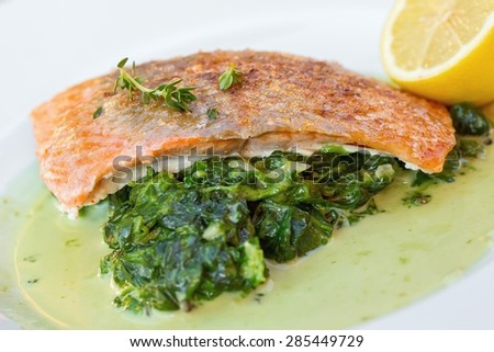 Grilled salmon with spinach, lemon and thyme - stock photo