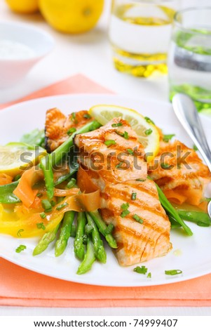 grilled salmon with spring asparagus on white plate, soft focus - stock photo