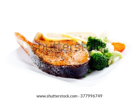 Grilled salmon with steamed vegetables on plate isolated on white background - stock photo