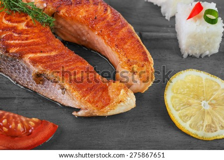 Grilled salmon with vegetables and rice on  wooden background - stock photo