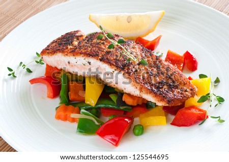Grilled salmon with vegetables, herbs and lemon - stock photo