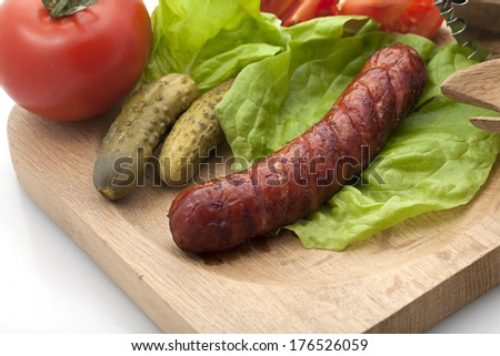Grilled sausage and vegetables on wooden plate