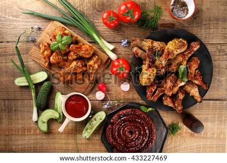 Grilled sausage, chicken leg and wings with vegetables and sauce on wooden background, selective focus