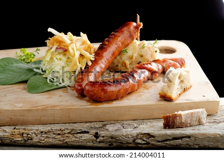 Grilled sausage with cabbage and mashed potatoon the wooden plate - stock photo