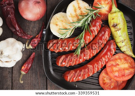 Grilled sausages and vegetables in grilling pan - stock photo