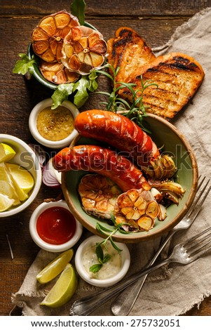 Grilled sausages, garlic and onions with different kinds of dips - stock photo