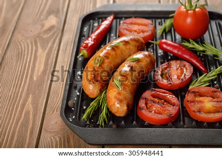 Grilled sausages on the grill pan on brown background - stock photo