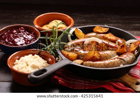 Grilled sausages with barbecue sauce baked in a frying pan - stock photo